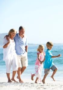 Grandparents and Grandchildren Walking Along Beach